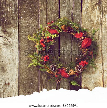 Christmas wreath with natural decorations hanging on a rustic wooden wall with snow and copy space.