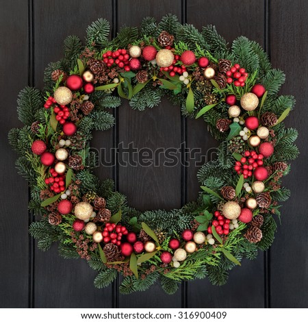 Christmas wreath with red and gold bauble decorations, bow, holly, mistletoe, pine cones and blue spruce fir over dark oak front door background.