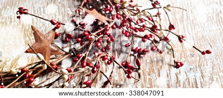 Christmas wreath with red and white berries and rusty metal stars on wooden background. Falling snow effect. Narrow format for web design. Vintage Style - stock photo