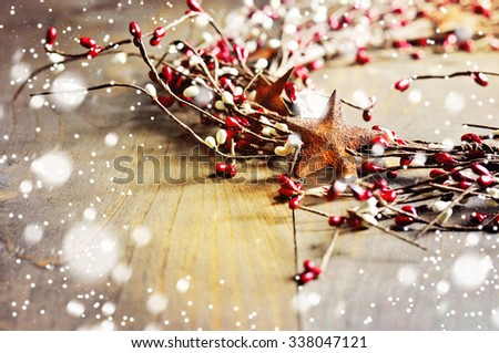Christmas wreath with red and white berries and rusty metal stars on wooden background. Falling snow effect. Vintage Style. Copy space. - stock photo