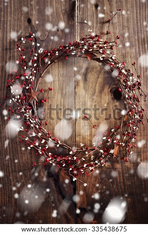 Christmas wreath with red and white berries and rusty metal stars on wooden background. Vintage Style. Falling snow effect. Toned image - stock photo