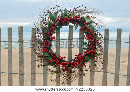Christmas wreath with red berries hanging on a beach fence - stock photo