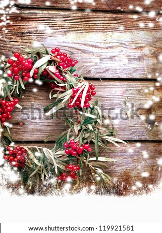 Christmas wreath with red berry  on a rustic wooden wall with copy space with a snow/holidays background - stock photo