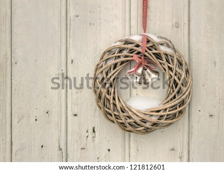 Christmas wreath with red ribbon and golden bells on a vintage wooden background - stock photo