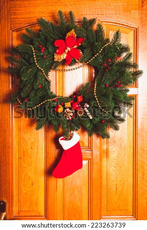 Christmas wreath with red sock on the door - stock photo