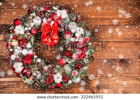 Christmas wreath with stars and snow on the wooden background - stock photo