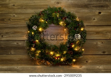 Christmas wreath with white lights on rustic wooden boards.  Low lighting to bring out glow of lights.  - stock photo