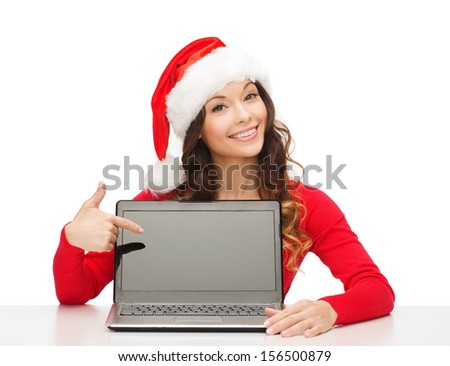 christmas, x-mas, electronics, gadget concept - smiling woman in santa helper hat with blank screen laptop computer - stock photo