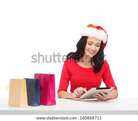 christmas, x-mas, online shopping concept - woman in santa helper hat with gift box and tablet pc computer - stock photo