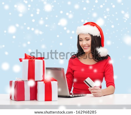 christmas, x-mas, online shopping concept - woman in santa helper hat with gift boxes, laptop computer and credit card - stock photo