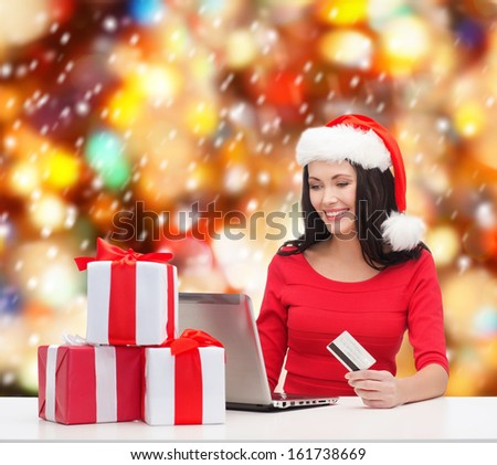 christmas, x-mas, online shopping, electronics concept - woman in santa helper hat with gift boxes, laptop computer and credit card - stock photo