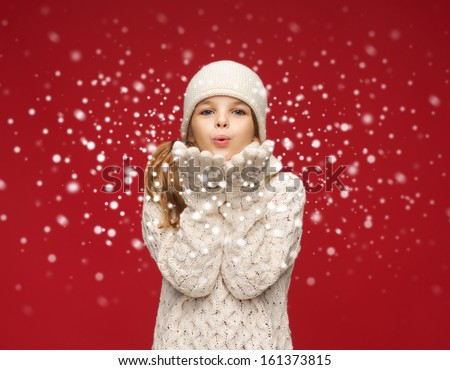 christmas, x-mas, people, happiness concept - happy girl in winter clothes blowing on palms - stock photo