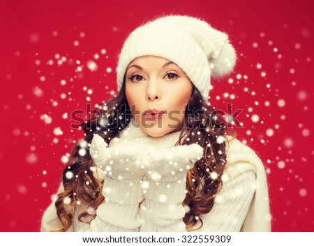 christmas, x-mas, people, happiness concept - happy woman in winter clothes blowing on palms - stock photo