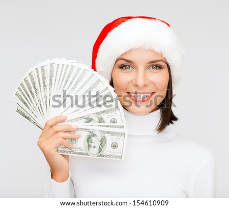 christmas, x-mas, sale, banking concept - smiling woman in santa helper hat with us dollar money - stock photo