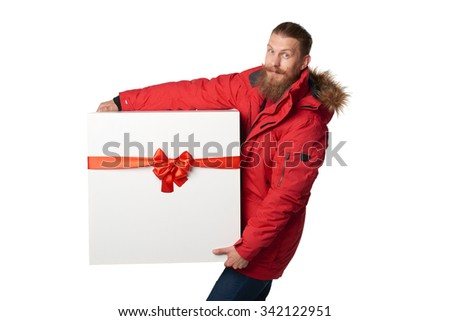 Christmas, x-mas, winter gift concept. Man wearing red winter jacket carrying huge heavy gift box with red bow, isolated on white - stock photo