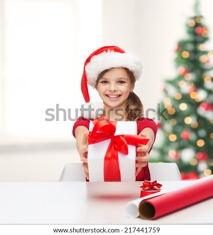 christmas, x-mas, winter, happiness concept - smiling girl in santa helper hat with gift box and wrapping paper - stock photo