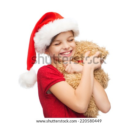 christmas, x-mas, winter, happiness concept - smiling girl in santa helper hat with teddy bear - stock photo