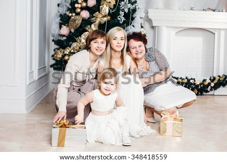 christmas, x-mas, winter, happiness concept - smiling happy family: grandmother, mother, daughter, granddaughter around the Christmas tree with gifts, 4 generations of the family, four, love concept - stock photo