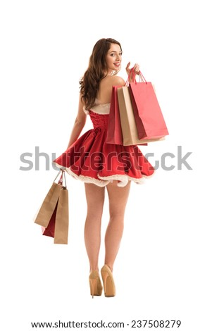 Christmas, x-mas, winter, happiness concept - smiling woman in Santa Claus dress with shopping bags - stock photo