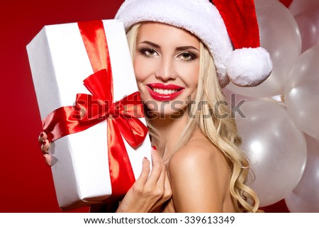 christmas, x-mas, winter, happiness concept - smiling woman in santa helper hat with many gift boxes. picture of cheerful santa helper girl with gift box - stock photo