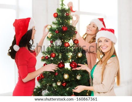 christmas, x-mas, winter, happiness concept - three smiling women in santa helper hats decorating a christmas tree - stock photo