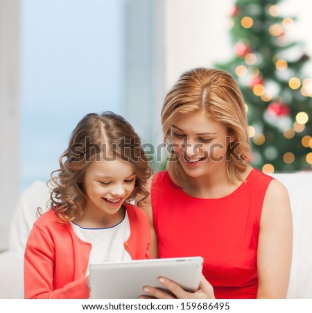 christmas, x-mas, winter, happiness, modern technology concept - mother and daughter with tablet pc
