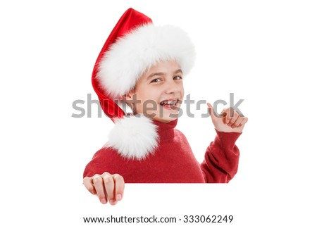 Christmas, Xmas holidays, the concept of advertising - happy teen boy in Santa hat pointing finger on white board. Object isolated on white background. It can be used as advertising - stock photo