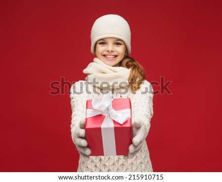 christmas, xmas, winter and happiness concept - smiling girl in hat, muffler and gloves with gift box - stock photo
