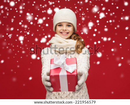 christmas, xmas, winter, happiness concept - smiling girl in hat, muffler and gloves with gift box - stock photo