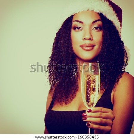 christmas young beautiful mulatto woman smiling with champagne and in santa's hat, toned - stock photo