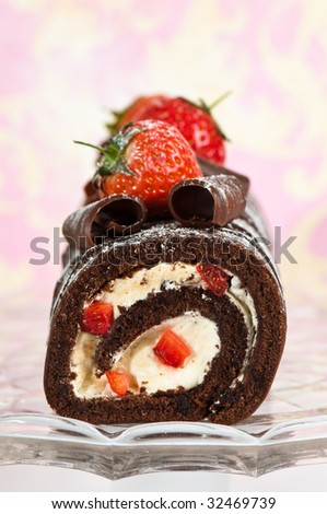 Christmas yule log decorated with chocolate curls and strawberries on glass comport - stock photo