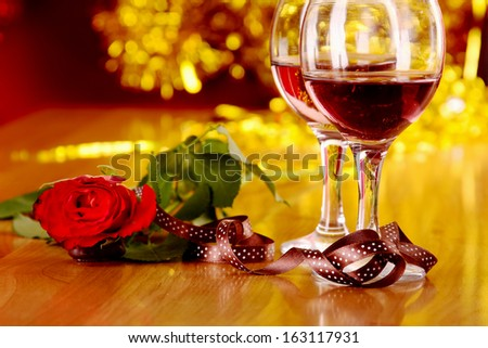 christmass dinner with rose candies and two glasses of red wine - stock photo