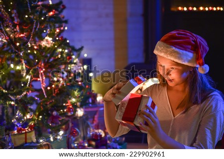 Christmastime, an expressive young girl with a santa hat opening her gift-box and finding a wonderful surprise in front of the christmas tree illuminated, in the warm atmosphere of christmas night - stock photo