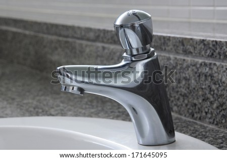 Chrome Faucet in toilet  - stock photo