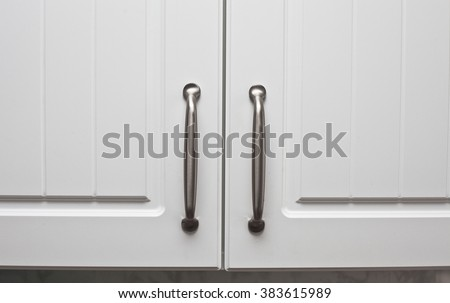 Chrome handles on a pair of wooden cupboard doors - stock photo