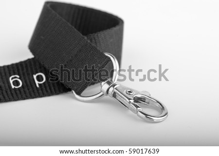 Chrome Key ring clip on curled up black lanyard on gradient background - stock photo