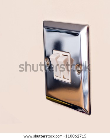 Chrome light switch on a magnolia wall - stock photo