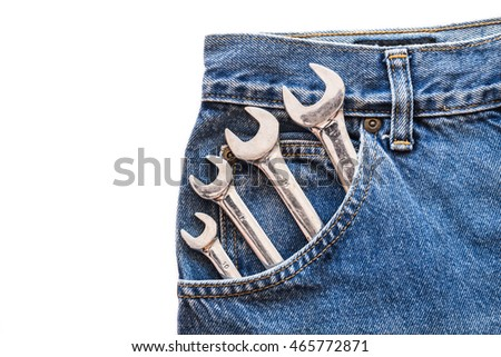 chrome lug wrench in front blue jeans pocket on white isolated background. Copy space for text