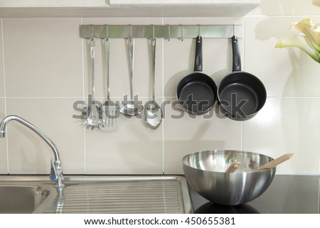Chrome pots, pans and utensils hanging in contemporary kitchen. - stock photo