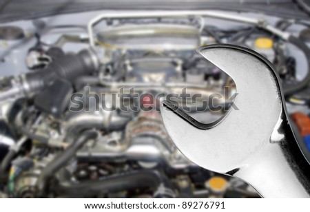 Chrome spanner with blurred car engine in the background - stock photo