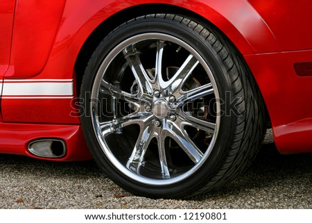 chrome sportscar alloy on red ford mustang - stock photo