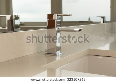 Chrome water faucet with marble counter tops and a white sink - stock photo
