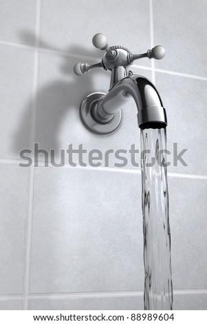 Chrome Water tap on tiles - stock photo