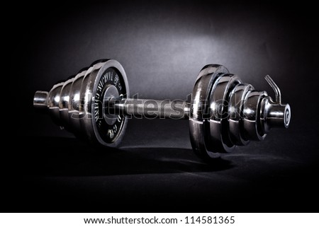 Chromed dumbbells weights over black background - stock photo