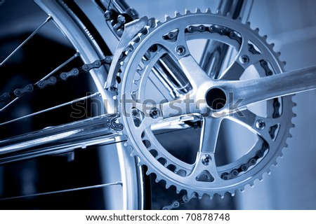 chromed precision racing bike gearwheels and chain with a blue tint - stock photo