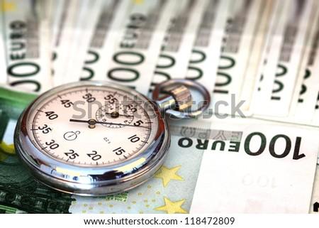 Chronometer and 100 euro bills close up - stock photo
