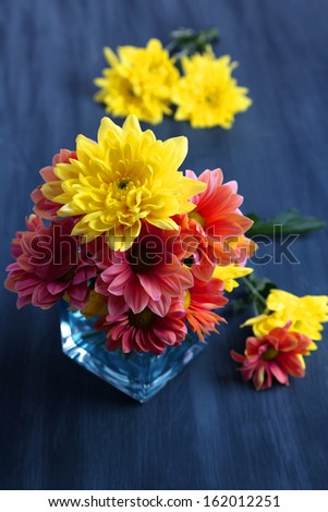 Chrysanthemum flowers in vase on wooden table close-up - stock photo