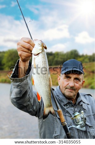chub in the hand of fisherman against the sky and the river - stock photo