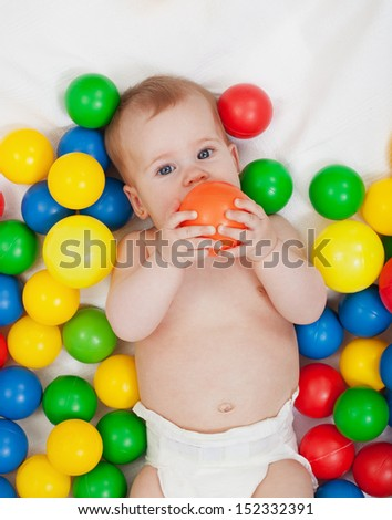 Chubby baby girl playing with colorful balls - tasting them - stock photo