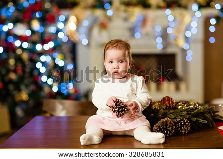 Chubby little cute baby girl in white dress sitting on the table in the New year, the Christmas lights and fireplace - stock photo